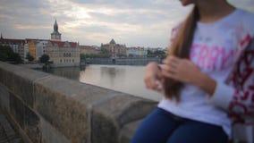 Το κορίτσι κάθεται στο στηθαίο της γέφυρας και αγγίζει την τρίχα απόθεμα βίντεο