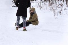 Το κορίτσι κάθεται στο χιόνι και περιμένει τον τύπο να την βοηθήσει να σηκωθεί στοκ εικόνα με δικαίωμα ελεύθερης χρήσης