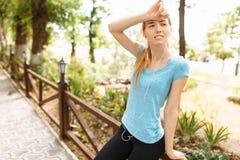 Το κορίτσι κάνει ένα σπάσιμο στην κατάρτιση, το υπόλοιπο από την ικανότητα και το τρέξιμο στο δρόμο στοκ φωτογραφία
