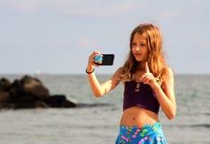 Το κορίτσι κάνει ένα selfie στην παραλία θάλασσας στοκ εικόνα με δικαίωμα ελεύθερης χρήσης