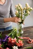 Το κορίτσι κάνει μια ανθοδέσμη πέρα από το γκρίζο υπόβαθρο, βάζοντας τα λουλούδια στο va στοκ φωτογραφία με δικαίωμα ελεύθερης χρήσης