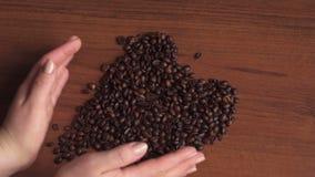 Το κορίτσι κάνει μια μορφή καρδιών από τα φασόλια καφέ απόθεμα βίντεο
