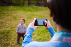 Το κορίτσι κάνει μια φωτογραφία του παιδιού στο smartphone Στοκ Φωτογραφία
