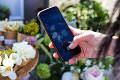 Το κορίτσι κάνει μια φωτογραφία των λουλουδιών στο τηλέφωνο Στοκ εικόνες με δικαίωμα ελεύθερης χρήσης