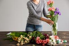 Το κορίτσι κάνει την ανθοδέσμη πέρα από το γκρίζο υπόβαθρο, βάζοντας τα λουλούδια στο βάζο Στοκ εικόνα με δικαίωμα ελεύθερης χρήσης