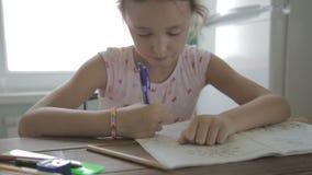 Το κορίτσι κάνει την εργασία για το δημοτικό σχολείο απόθεμα βίντεο