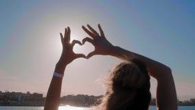 Το κορίτσι κάνει την καρδιά με τα χέρια της πέρα από το υπόβαθρο θάλασσας Η σκιαγραφία παραδίδει τη μορφή καρδιών με το ηλιοβασίλ απόθεμα βίντεο