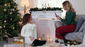 Το κορίτσι κάνει τη φωτογραφία το κινητό τηλέφωνο, η φίλη προετοιμάζεται για τη Παραμονή Χριστουγέννων, συζήτηση γυναικών, γέλιο, φιλμ μικρού μήκους