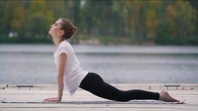 Το κορίτσι κάνει τον αθλητισμό κοντά στη λίμνη φιλμ μικρού μήκους
