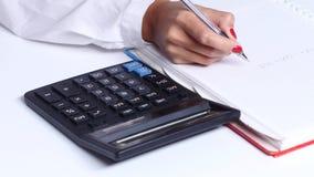 Το κορίτσι κάνει τους υπολογισμούς και γράφει τους αριθμούς σε ένα σημειωματάριο κλείστε επάνω απόθεμα βίντεο