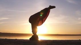 Το κορίτσι κάνει το asana στη γιόγκα, αυξάνει αργά τα πόδια της στο ράφι στο κεφάλι της Σκιαγραφία μιας γυναίκας στο υπόβαθρο φιλμ μικρού μήκους
