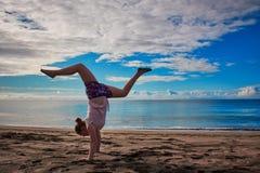 Το κορίτσι κάνει handstand στην παραλία στοκ φωτογραφία