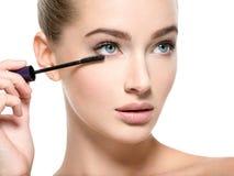 Το κορίτσι κάνει makeup Η γυναίκα εφαρμόζει mascara στα eyelashes στοκ εικόνες με δικαίωμα ελεύθερης χρήσης