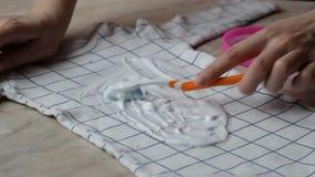 Το κορίτσι καθαρίζει επάνω τους λεκέδες στα ενδύματα μωρών με remover λεκέδων, κινηματογράφηση σε πρώτο πλάνο, στεγνός καθαρισμός απόθεμα βίντεο