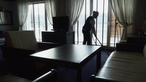 Το κορίτσι καθαρίζει το πάτωμα με την ηλεκτρική σκούπα στο σύγχρονο ξενοδοχείο απόθεμα βίντεο