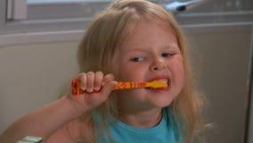 Το κορίτσι καθαρίζει τα δόντια του απόθεμα βίντεο