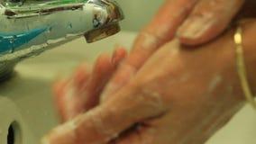 Το κορίτσι καθαρίζει τα χέρια με το σαπούνι κάτω από τη βρύση φιλμ μικρού μήκους