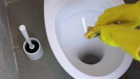 Το κορίτσι καθαρίζει την τουαλέτα στα κίτρινα λαστιχένια γάντια με ένα σφουγγάρι απόθεμα βίντεο