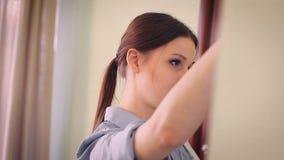Το κορίτσι καθαρίζει τον καθρέφτη φιλμ μικρού μήκους