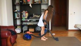 Το κορίτσι καθαρίζει τον τάπητα στο δωμάτιο με μια ηλεκτρική σκούπα απόθεμα βίντεο