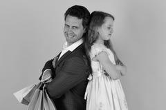 Το κορίτσι και το άτομο με τα πρόσωπα χαμόγελου στέκονται πίσω να υποστηρίξουν και να κρατήσουν τις τσάντες αγορών στο ρόδινο υπό Στοκ Εικόνα