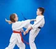 Το κορίτσι και το αγόρι στο karategi εκπαιδεύουν το βραχίονα διατρήσεων και το πόδι λακτίσματος Στοκ Εικόνες