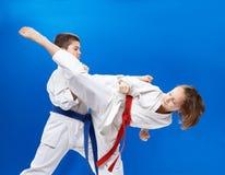 Το κορίτσι και το αγόρι στο karategi εκπαιδεύουν karate τα χτυπήματα Στοκ Εικόνα