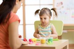 Το κορίτσι και η μητέρα παιδιών παιδιών παίζουν το ζωηρόχρωμο παιχνίδι αργίλου στο βρεφικό σταθμό ή τον παιδικό σταθμό Στοκ Φωτογραφία