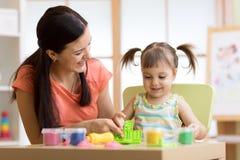 Το κορίτσι και η μητέρα παιδιών παιδιών παίζουν το ζωηρόχρωμο παιχνίδι αργίλου στο βρεφικό σταθμό ή τον παιδικό σταθμό Στοκ φωτογραφίες με δικαίωμα ελεύθερης χρήσης