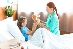 Το κορίτσι και η νοσοκόμα που κρατούν teddy αντέχουν στο δωμάτιο νοσοκομείων Στοκ Εικόνες