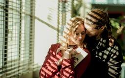 Το κορίτσι και ο άνδρας κοντά στο παράθυρο, ogle άνδρας, χαριτωμένες σχέσεις, συνδέουν το ερωτευμένο, ξανθό κορίτσι, που χαμογελά Στοκ Φωτογραφία