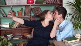Ο τύπος και το κορίτσι κάθονται στην εγχώρια βιβλιοθήκη Το κορίτσι και ο τύπος θέτουν, παίρνουν ένα selfie, κατόπιν φιλί φιλμ μικρού μήκους