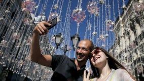 Το κορίτσι και ο τύπος κάνουν μια φωτογραφία στην οδό στο υπόβαθρο των λαμπτήρων οδών στο καλώδιο Οι λαμπτήρας-λαμπτήρες κρεμούν απόθεμα βίντεο