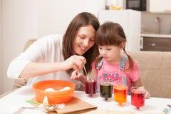 Το κορίτσι και τα αυγά χρωμάτων μητέρων της στο σπίτι Στοκ Φωτογραφίες