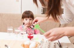 Το κορίτσι και τα αυγά χρωμάτων μητέρων της στο σπίτι Στοκ Φωτογραφία