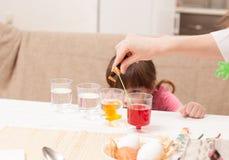 Το κορίτσι και τα αυγά χρωμάτων μητέρων της στο σπίτι Στοκ φωτογραφία με δικαίωμα ελεύθερης χρήσης