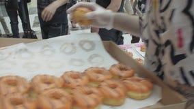 Το κορίτσι και το άτομο βάζουν ζωηρόχρωμα doughnuts στον πίνακα στο εμπορικό κέντρο δίκαιος άνθρωποι απόθεμα βίντεο