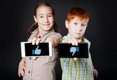 Το κορίτσι και το αγόρι, παιδιά παρουσιάζουν κινητό με τον αντίχειρα επάνω κάτω Στοκ Φωτογραφίες