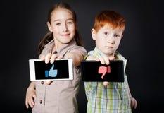 Το κορίτσι και το αγόρι, παιδιά παρουσιάζουν κινητό με τον αντίχειρα επάνω κάτω Στοκ εικόνες με δικαίωμα ελεύθερης χρήσης