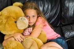 Το κορίτσι και teddy αφορά τον καναπέ Στοκ φωτογραφία με δικαίωμα ελεύθερης χρήσης