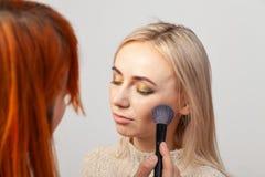 Το κορίτσι καλλιτεχνών Makeup με την κόκκινη τρίχα βάζει τη σύνθεση σε ένα ξανθό πρότυπο με τις προσοχές ιδιαίτερες, κρατά μια βο στοκ εικόνες