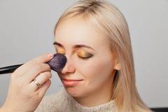 Το κορίτσι καλλιτεχνών Makeup με την κόκκινη τρίχα βάζει τη σύνθεση σε ένα ξανθό πρότυπο με τις προσοχές ιδιαίτερες, κρατά μια βο στοκ φωτογραφίες με δικαίωμα ελεύθερης χρήσης
