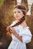 Το κορίτσι το καλοκαίρι στον τομέα κοντά στη θυμωνιά χόρτου στοκ εικόνες