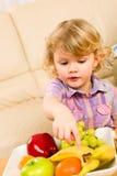 το κορίτσι καρπού μπανανών λίγα που δείχνουν θέλει Στοκ Εικόνες