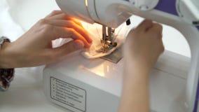 Το κορίτσι καρφώνει ένα σχέδιο στα χέρια fabricFemale ράβει σε μια ράβοντας μηχανή απόθεμα βίντεο