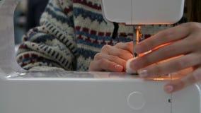 Το κορίτσι καρφώνει ένα σχέδιο στο ύφασμα που τα θηλυκά χέρια ράβουν σε μια ράβοντας μηχανή απόθεμα βίντεο