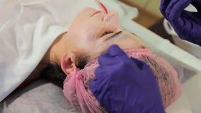 Το κορίτσι κατά τη διάρκεια της πυράκτωσης του BB διαδικασίας Η γυναίκα με την παραλαβή στο beautician Η διαδικασία τη μάσκα απόθεμα βίντεο
