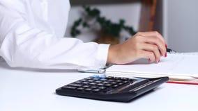 Το κορίτσι καταγράφει τους υπολογισμούς σε ένα σημειωματάριο που λαμβάνεται στον υπολογιστή κλείστε επάνω απόθεμα βίντεο