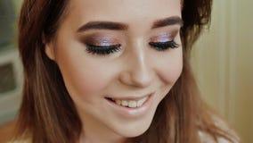 Το κορίτσι καταδεικνύει το εύγευστο makeup της Κλείστε επάνω το πορτρέτο της νέας όμορφης γυναίκας με τη μακριά σγουρή τρίχα brun φιλμ μικρού μήκους
