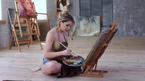 Το κορίτσι καλλιτεχνών επισύρει την προσοχή τη συνεδρίαση εικόνων στο πάτωμα στο εργαστήριο τέχνης φιλμ μικρού μήκους